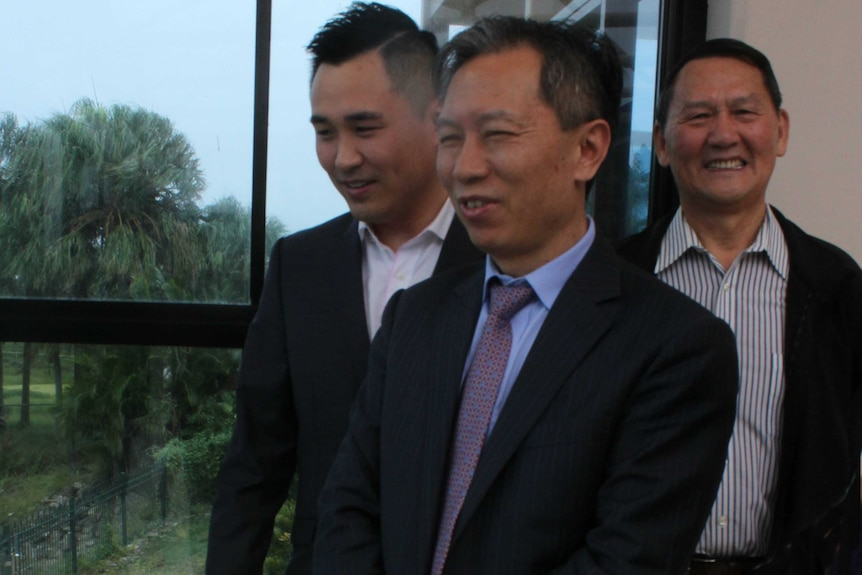 Three Chinese men standing in front of a window with trees in background