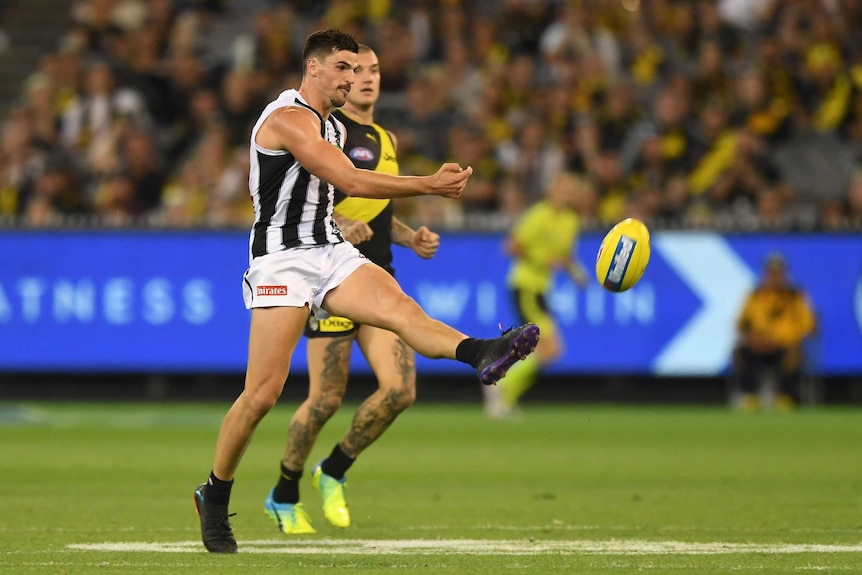 An AFL player kicks the ball in the midfield, as an opponent fails to get close enough to stop him.
