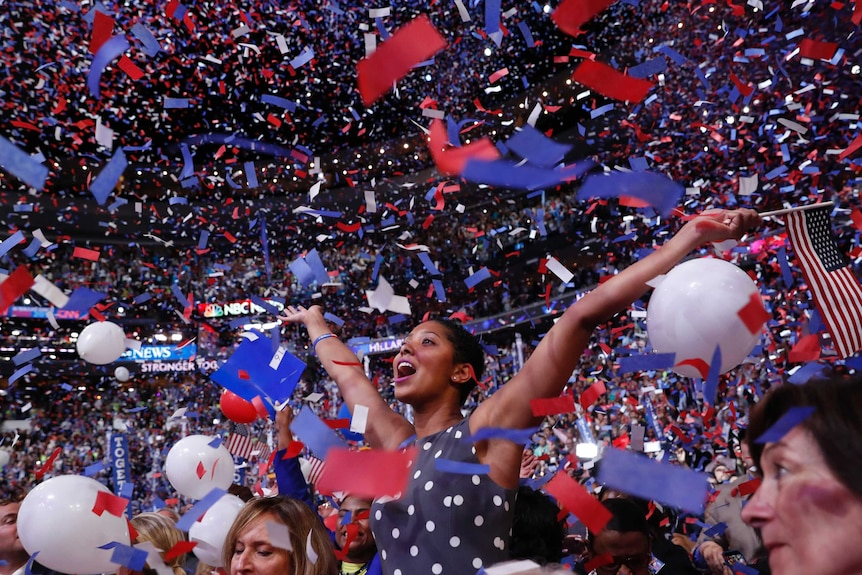A woman in a polka dot dress waves an American flag as confetti and balloons fall around her