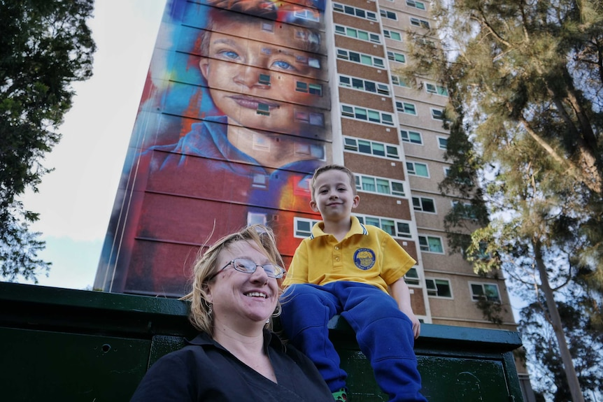 Six-year-old Arden Watson-Cropley with his mum in front of a mural of his face painted on a Collingwood housing commission flat.