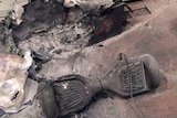 A charred toy hoverboard with fire-damaged packaging and floor.