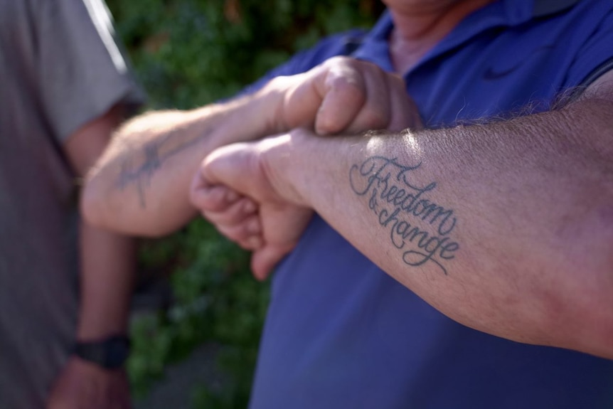 """The words """"freedom and change"""" tattooed on a man's arm."""