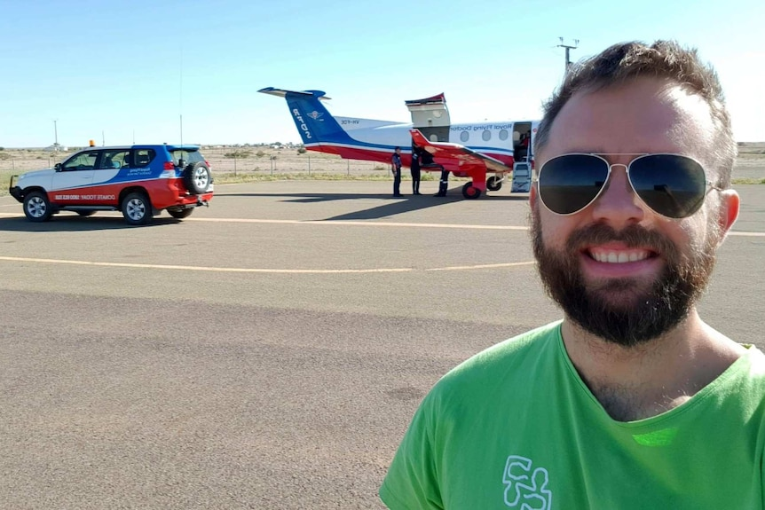 A man wearing a green shirt and black sunglasses with brown hair and a beard smiles at the camera in front of an RFDS plane.