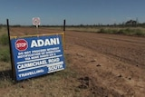 Sign reading Adani on the dirt road to it Carmichael mine site