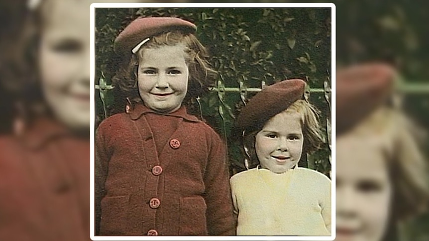 Rose Collins wears a white shirt and red hat standing next to her older sister dressed in a red shirt and cardigan with red hat
