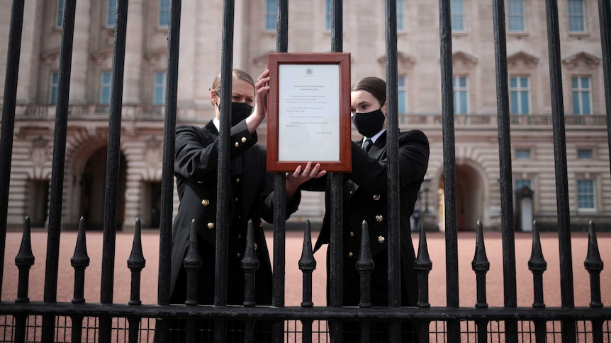 Two women place a notice on the gates of Buckingham Palace.