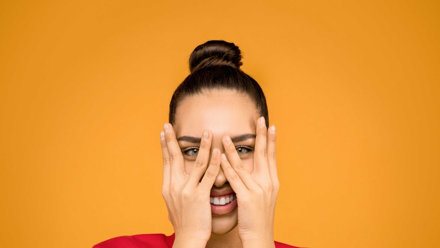 A woman stares at the camera while covering her face with her hands.