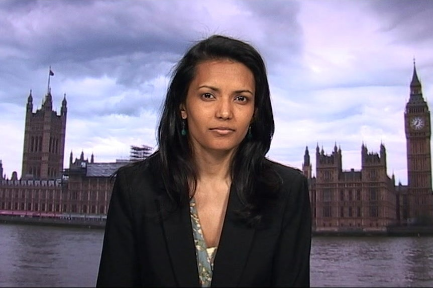 A woman with dark hair sits in front of an image of London.
