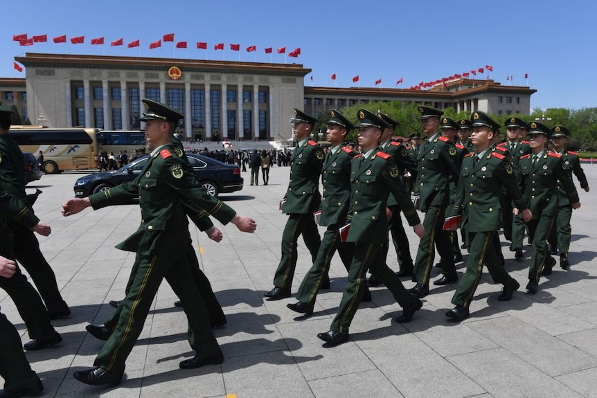 Paramilitary police officers dressed in green uniforms march in Tiananmen Square.