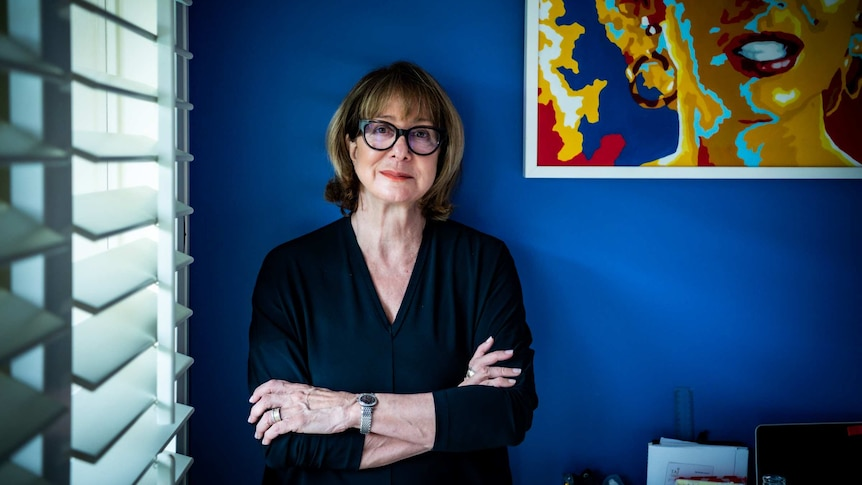 A woman with black glasses up against a blue wall