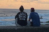 "Two people sitting watching surfers, seen from behind — the woman's T-shirt says ""Anti social social club"""