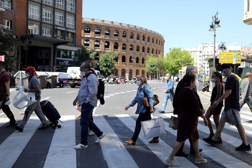 People wearing face masks walk across a pedestrian crossing in front of an amphitheatre