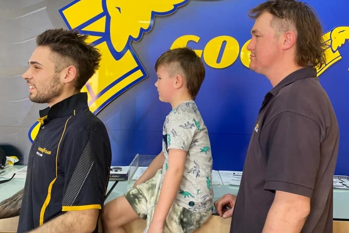 Two men and a boy stand facing the left, to show off the side profile of their mullets.