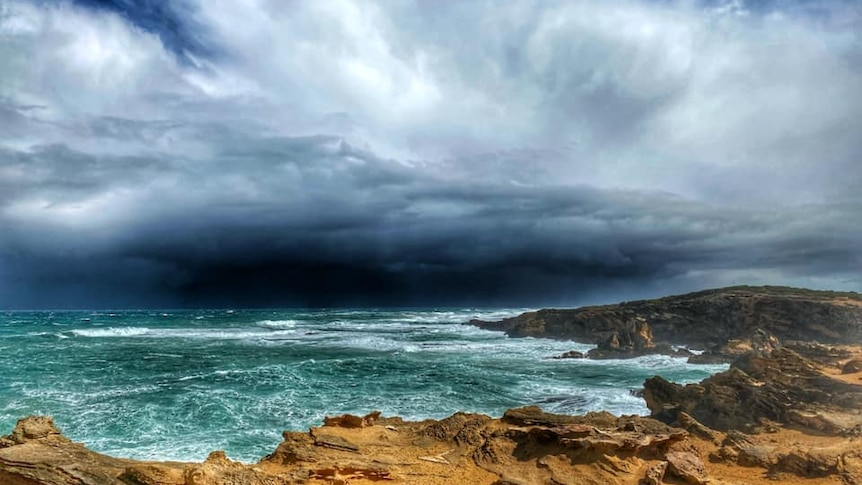Ominous dark storm clouds over a churning ocean