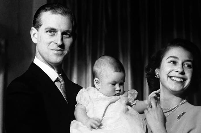A black and white photo of Prince Philip in a suit holding baby Prince Charles while the Queen looks off to the side.
