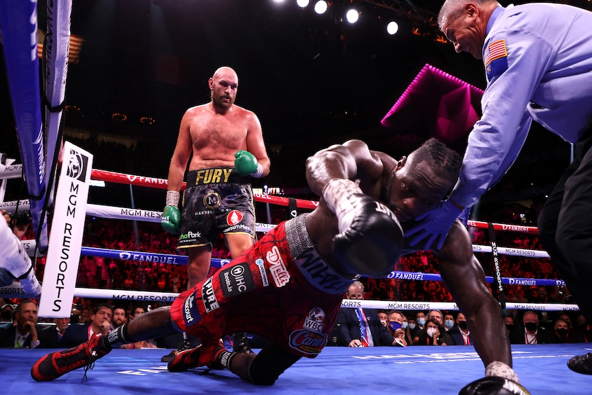 Deyontay Wilder falls face first to the ground with a man in a blue shirt trying to catch him and Tyson Fury watching on