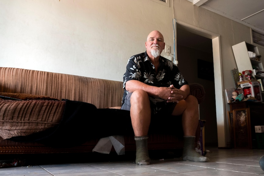 A man sits on a lounge chair in a family home.