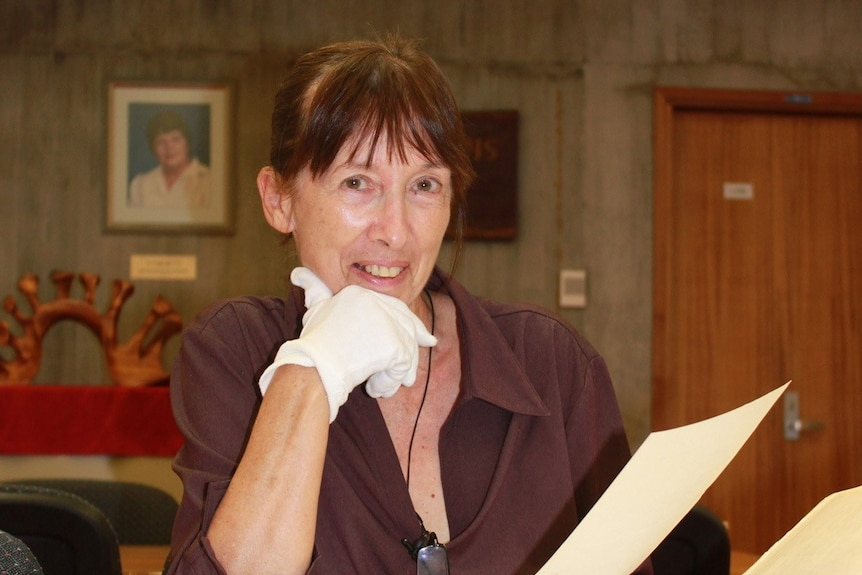 A woman wearing a white glove on one hand smiles as she holds up a document.
