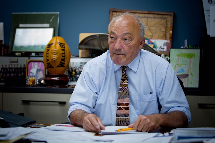 Michael Freelander sits at a desk covered with papers, in his office.