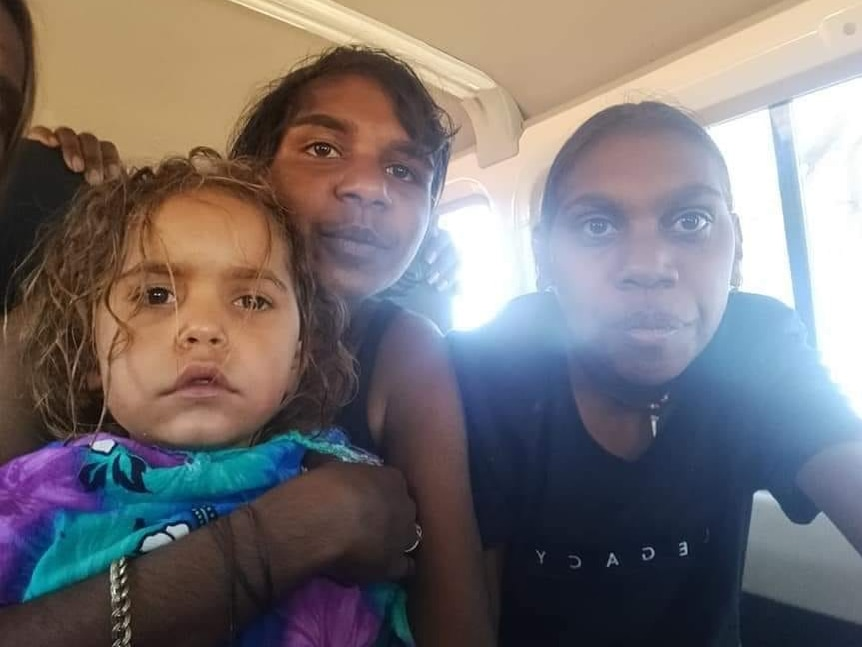 A four-year-old girl who spent more than 24 hours missing in the desert looks blankly at the camera with two smiling young girls