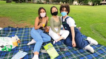 Photo of three women enjoying a picnic in Melbourne in December 2020.