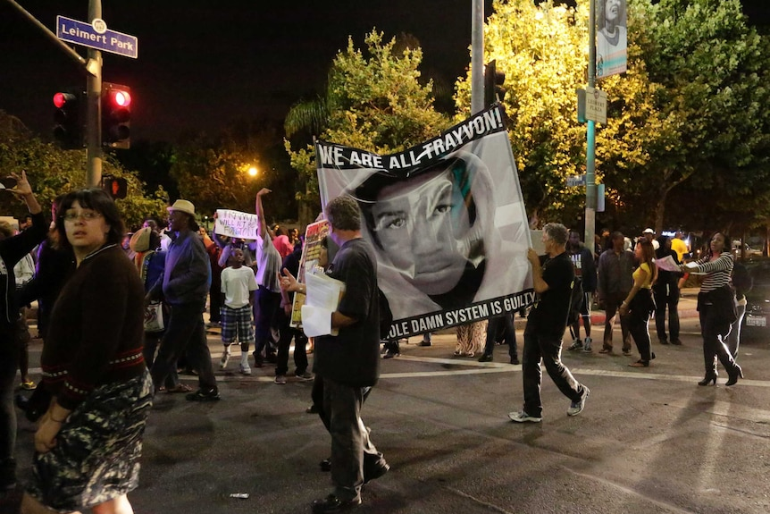 """Protesters hold up a banner reading """"We are all Trayvon. The whole damn system is guilty."""""""