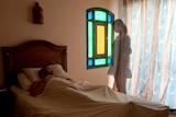 A man lying in bed and a ghost woman watching him
