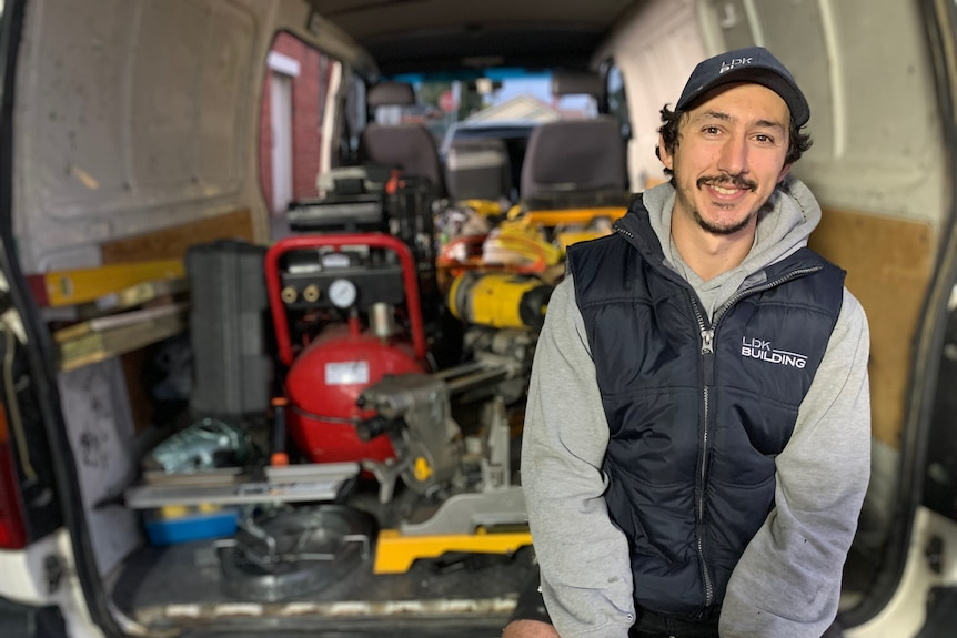 CarpenterLuke Kyriakides sits in the back of a white van wearing a puffer vest and cap, with tools behind him.
