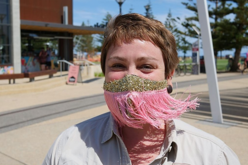 A woman wears a pink mask with tassels on a waterfront