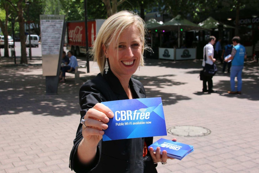 A woman smiles at the camera holding a card that reads 'CBRfree'.