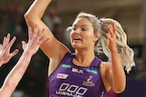 A netballer jumps up and extends her arm as she prepares to pass over the defence.