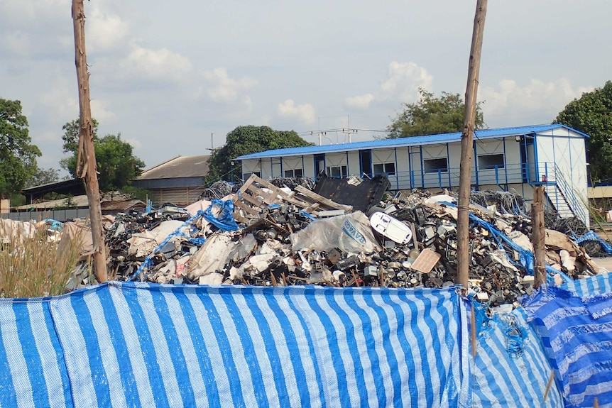 Huge piles of rubbish behind a plastic fence