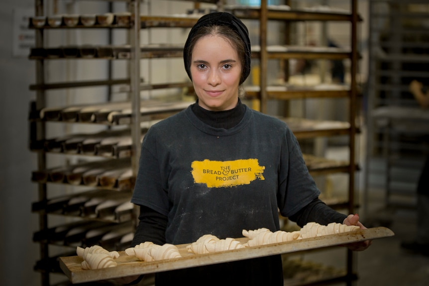 Lina stands with a tray of unbaked croissants.