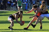 Three young footballer players fight for ball, left player is dodging two players on right