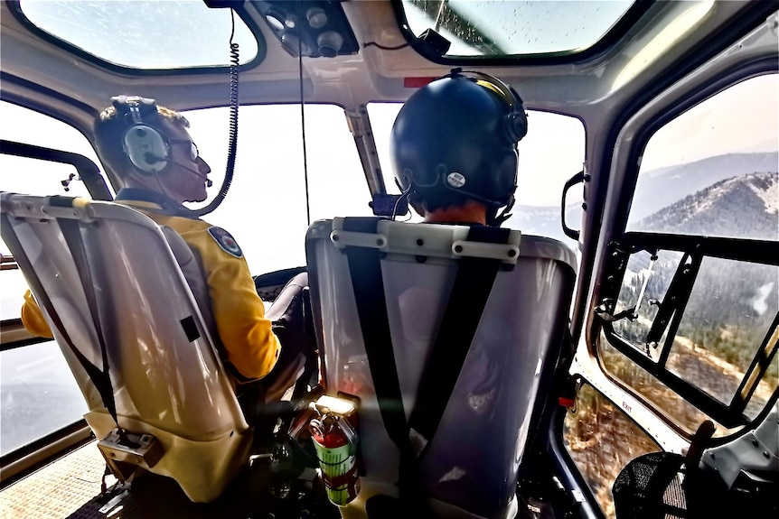 James Koens sits alongside another pilot in a helicopter flying over a bushfire.