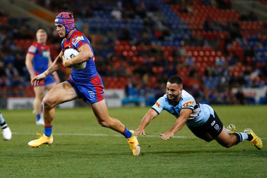 A Newcastle Knights NRL player runs with the ball tucked under his left arm as a Cronulla opponent dives to tackle him.