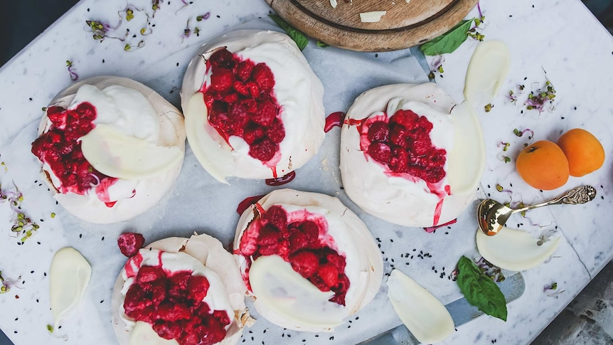 Five mini pavlovas with cream, white chocolate and raspberries presented on a marble table.