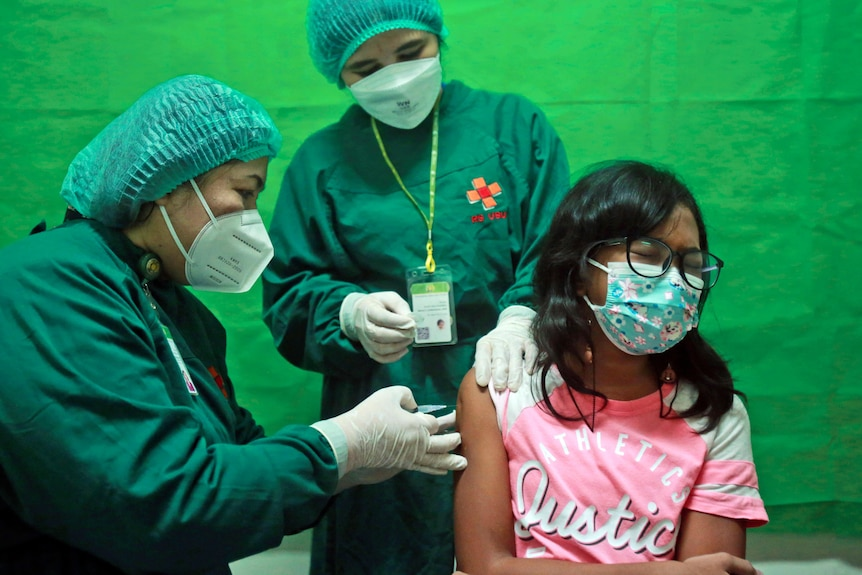 A young girl reacts to a shot of the Sinovac COVID-19 vaccine