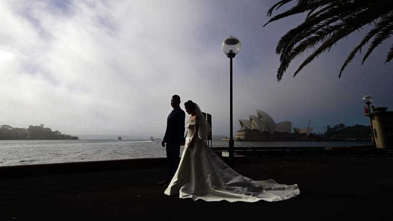 A couple in bridal dress with the opera house as backdrop.