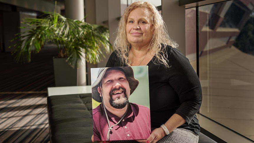 A woman holding a photo of a man.