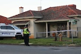 A brick and tile house with police tape, a police car and two officers out the front.