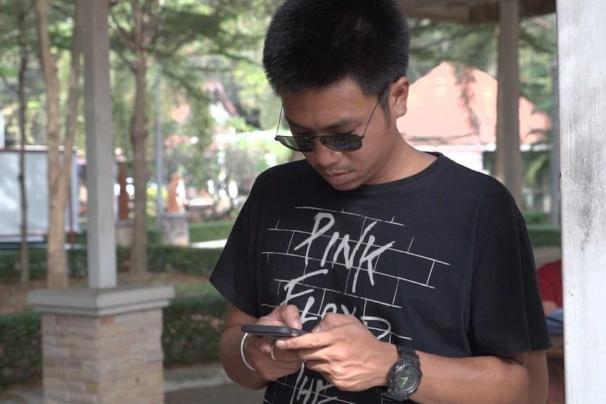 Law student Jatupat Boonpattararaksa wears a Pink Floyd shirt and looks down at his phone.