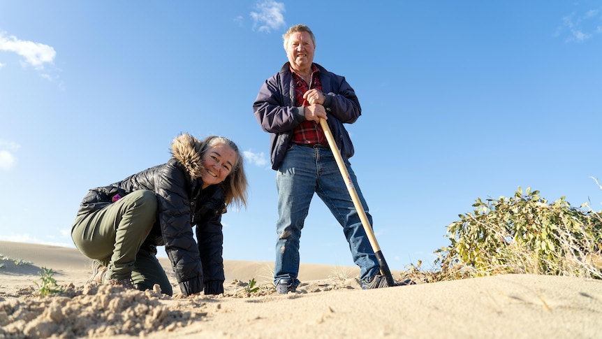 A man stands holding a shovel while a woman digs with her hands.