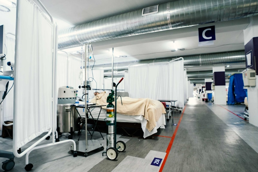 A patient in a hospital bed set up in a carpark