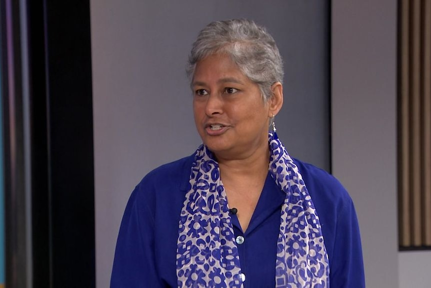 An older woman of east asian decent with grey hair in a purple shirt