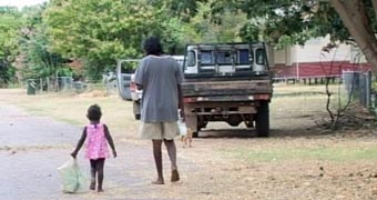 A man and a little girl walking along a road in Oombulgurri before settlement demolished