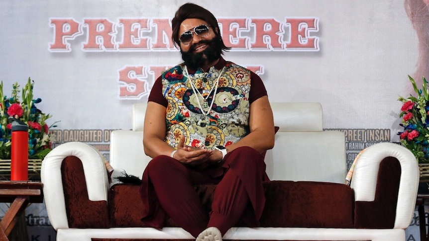 Rahim Singh sits on a couch. He is wearing sunglasses and a colourful vest. He is bearded and rotund.