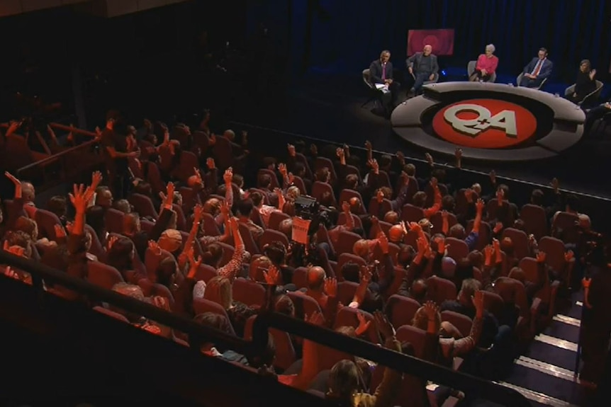 Audience members on the Q+A set raise their hands