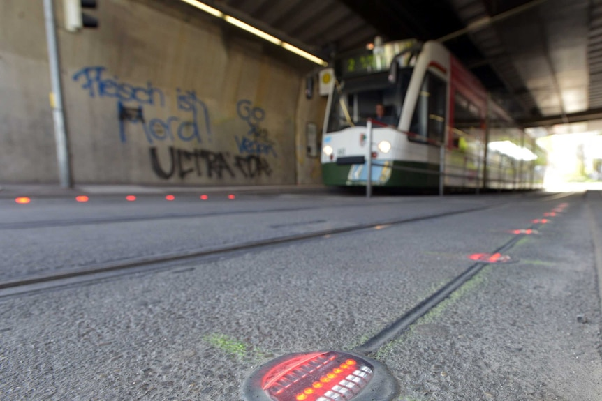 Red lights in the ground in front of a tram.