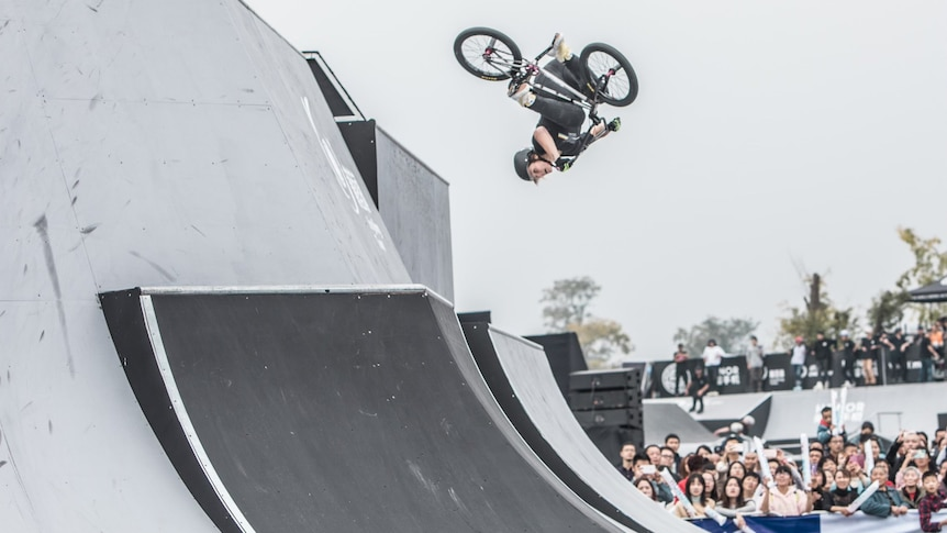 A woman doing a flip on a BMX bicycle as a crowd cheers